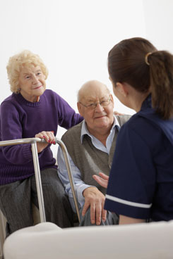 Young nurse talking with senior couple Indoors